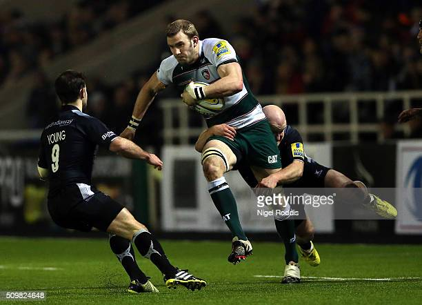Tom Croft of Leicester Tigers tackled by Michael Young and Scott Lawson of Newcastle Falcons during the Aviva Premiership match between Newcastle...