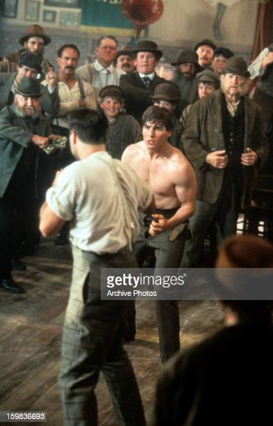 Tom Cruise about to get into fist fight with man while crowd watches in a scene from the film 'Far And Away' 1992