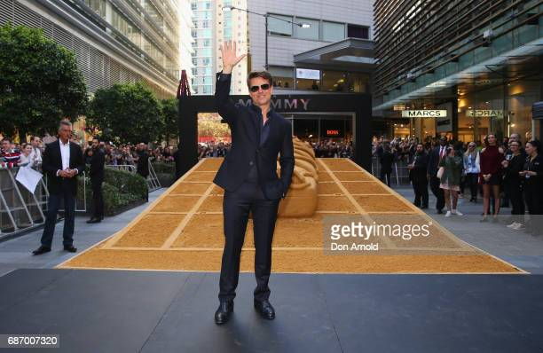 Tom Cruise gestures towards the crowd during a photo call for The Mummy at World Square on May 23 2017 in Sydney Australia
