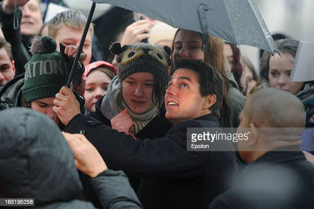 Tom Cruise shelters from the rain as he attends the film premiere of 'Oblivion' at the Oktyabr cinema hall on April 1 2013 in Moscow Russia
