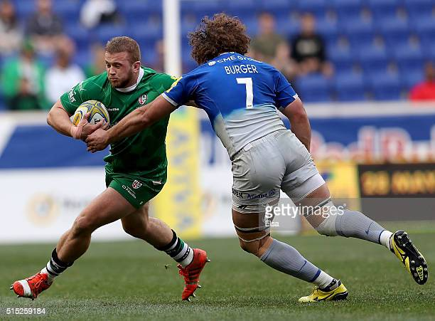 Tom Cruse of London Irish carries the ball as Jacques Burger of Saracens defends during the Aviva Premiership match on March 12 2016 at Red Bull...