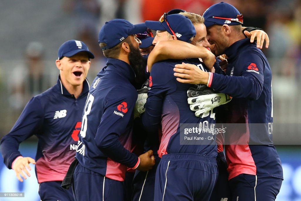 Tom Curran of England celebrates the wicket of Tim Paine of Australia with team mate and winning game five of the One Day International match between Australia and England at Perth Stadium on January 28, 2018 in Perth, Australia.