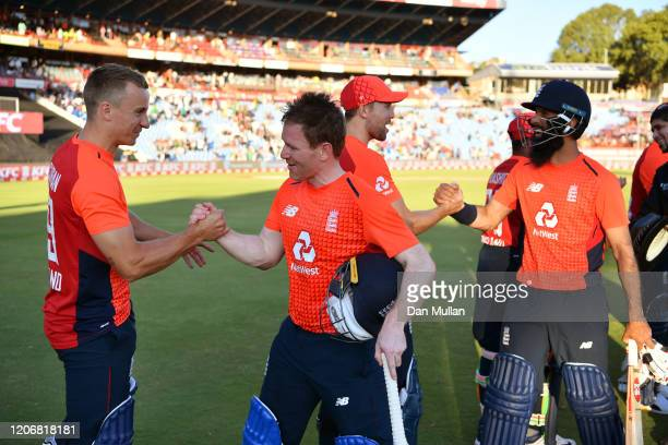 Tom Curran of England celebrates with Eoin Morgan of England as Dawid Malan of England embraces Moeen Ali of England following their victory during...