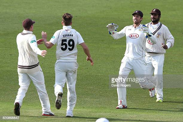 Tom Curran of Surrey is congratulated after taking the wicket of Greg Smith during the Specsavers County Championship division one match between...