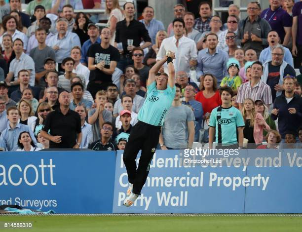 Tom Curran of Surrey makes a catch to stop the boundary and then releases the ball before he falls over the boundary rope during the NatWest T20...