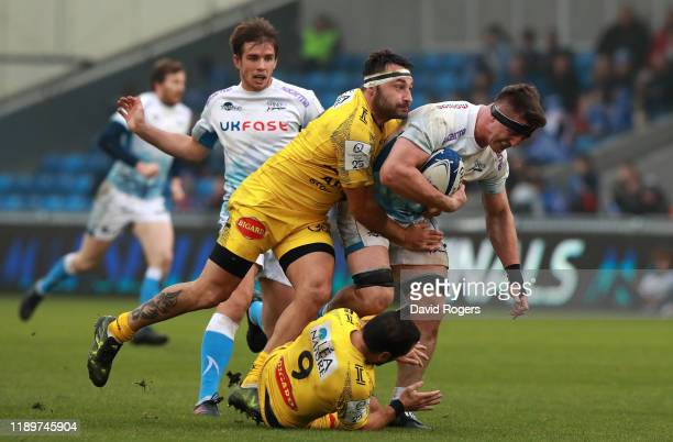 Tom Curry of Sale Sharks is tackled by Jeremy Sinzelle and Alexi Bales during the Heineken Champions Cup Round 2 match between Sale Sharks and La...