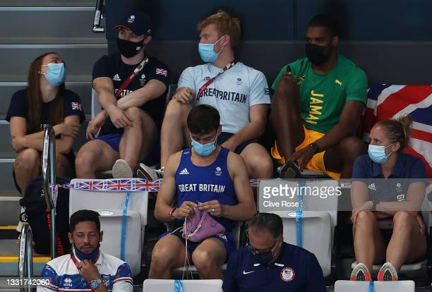 Tom Daley of Great Britain knits as he watches the Women's 3m Springboard Final on day nine of the Tokyo 2020 Olympic Games at Tokyo Aquatics Centre...