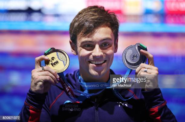 Tom Daley of Great Britain pose with his gold medal from the Men's 10m Platform and his silver medal from the mixed 3m Synchro Springbord during day...