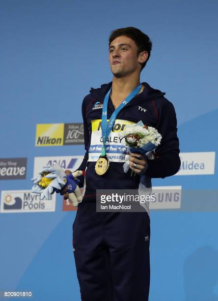 Tom Daley of Great Britain poses with his gold medal from the Men's 10m Platform during day nine of the FINA World Championships at the Duna Arena on...
