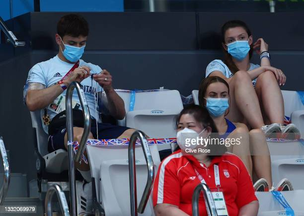 Tom Daley of Team Great Britain is seen knitting in the stands during the Men's 3m Springboard Final on day eleven of the Tokyo 2020 Olympic Games at...