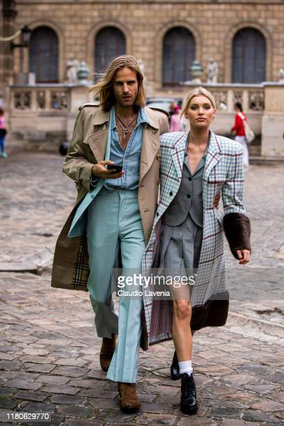 Tom Daly wearing a denim shirt teal blue suit brown shoes and beige trench coat and Elsa Hosk wearing a grey blazer with matching skirt checked coat...