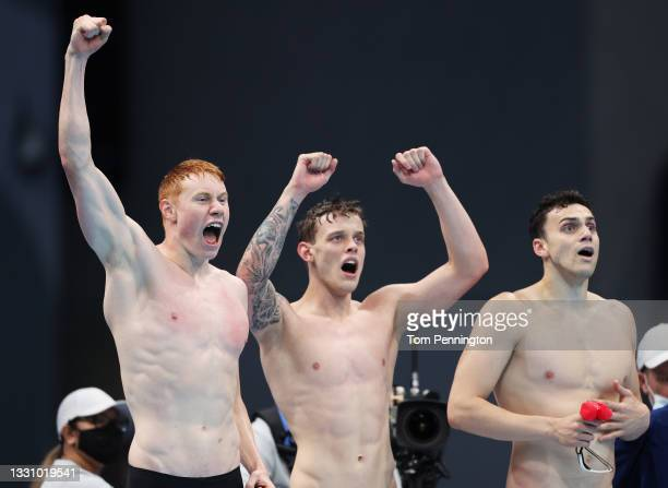Tom Dean, James Guy and Matthew Richards of Team Great Britain react as teammate Duncan Scott swims the anchor leg during the Men's 4 x 200m...