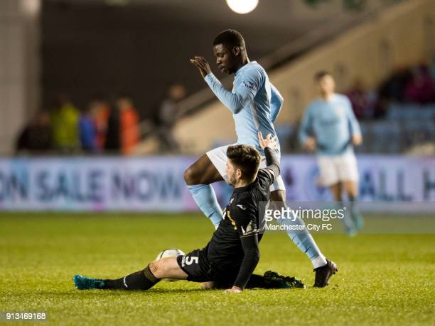 Tom Dele Bashiru of Manchester City is tackled by Cian Harries of Swansea city during the Manchester City v Swansea City match at Manchester City...