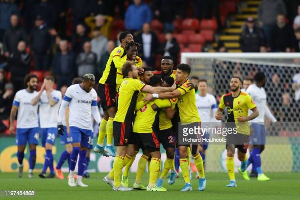 Tom Dele-Bashiru of Watford celebrates with teammates after scoring his team's first goal during the FA Cup Third Round match between Watford FC and...