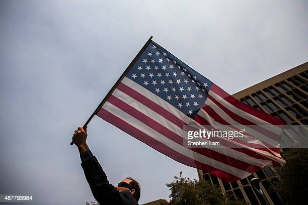 Tom DeWitt of Sacramento waves an American flag during a parade honoring Alek Skarlatos Anthony Sadler and Spencer Stone for their August 21 actions...