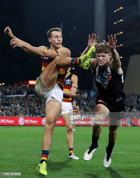 Tom Doedee of the Crows gets his kick away from Mitch Georgiades of the Power who attempted to smother the ball during the 2021 AFL Round 08 match...