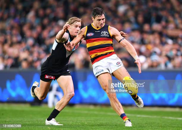 Tom Doedee of the Crows kicks away under pressure from Miles Bergman of Port Adelaide during the round eight AFL match between the Port Adelaide...