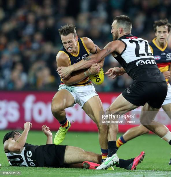 Tom Doedee of the Crows tries to get over Connor Rozee who is on the ground and Charlie Dixon during the 2021 AFL Round 08 match between the Port...