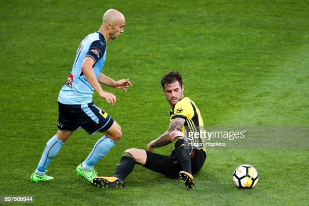 Tom Doyle of the Phoenix loses control of the ball under pressure from Adrian Mierzejewski of Sydney FC during the round 12 ALeague match between the...