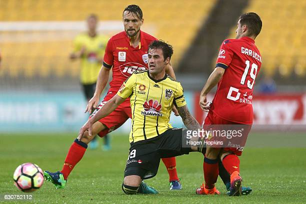 Tom Doyle of the Phoenix passes under pressure from Ben Garuccio of Adelaide United during the round 13 ALeague match between Wellington Phoenix and...