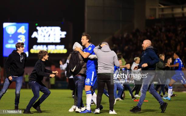 Tom Eastman of Colchester United celebrates with fans as they invade the pitch following victory in the penalty shoot out during the Carabao Cup...