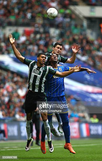 Tom Elliot of AFC Wimbledon is sandwiched between Jake Jervis and Carl McHugh of Plymouth during the Sky Bet League 2 Play Off Final between Plymouth...