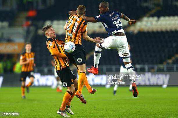 Tom Elliott of Millwall FC wins a header from Michael Dawson as teammate Angus MacDonald challenges during the Sky Bet Championship match between...