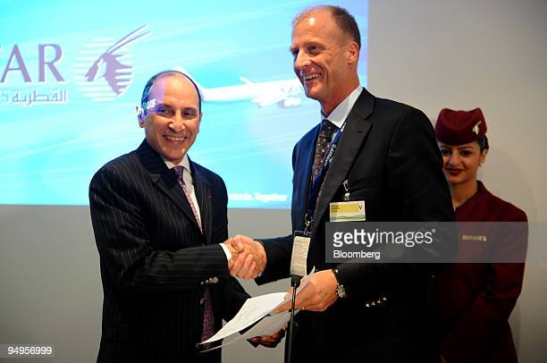 Tom Enders chief executive officer of Airbus SAS right shakes hands with Akbar Al Baker chief executive officer of Qatar Airways during a joint press...