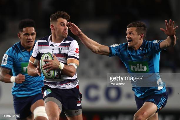 Tom English of the Rebels escapes the tackled of Matt Duffie of the Blues during the round 16 Super Rugby match between the Blues and the Rebels at...