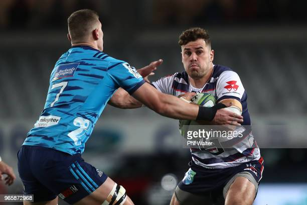 Tom English of the Rebels is tackled by Dalton Papalii of the Blues during the round 16 Super Rugby match between the Blues and the Rebels at Eden...