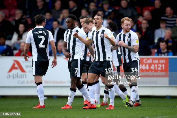 Tom Evans of Gillingham celebrates with his teammates after scoring his sides fourth goal during the Sky Bet League One match between AFC Wimbledon...