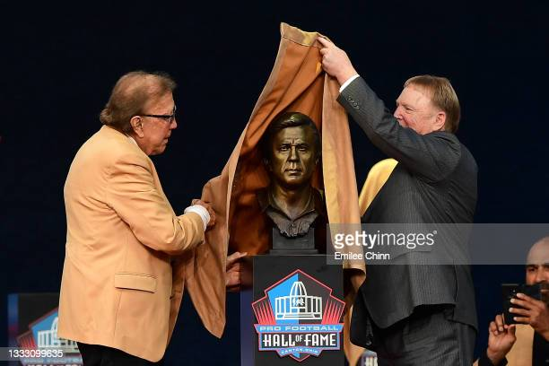 Tom Flores unveils his bust with Mark Davis during the NFL Hall of Fame Enshrinement Ceremony at Tom Benson Hall Of Fame Stadium on August 08, 2021...