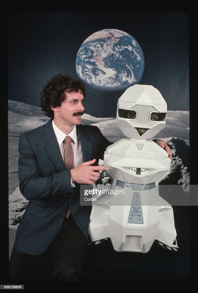 Executive Holding a Robot : News Photo