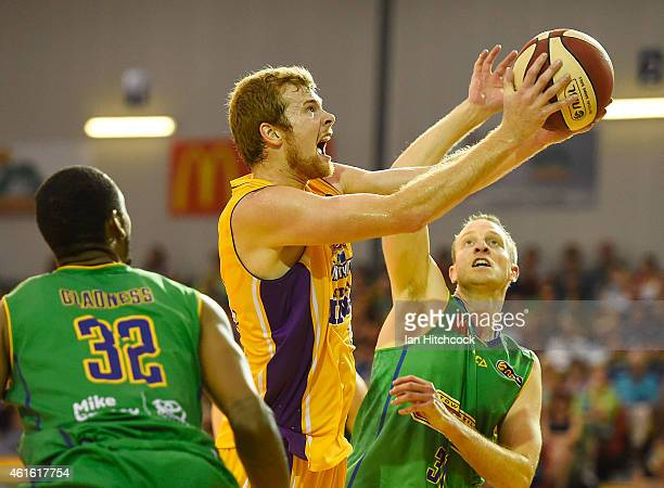 Tom Garlepp of the Kings attempts a layup past Jacob Holmes and Mickell Gladness of the Crocodiles during the round 15 NBL match between the...