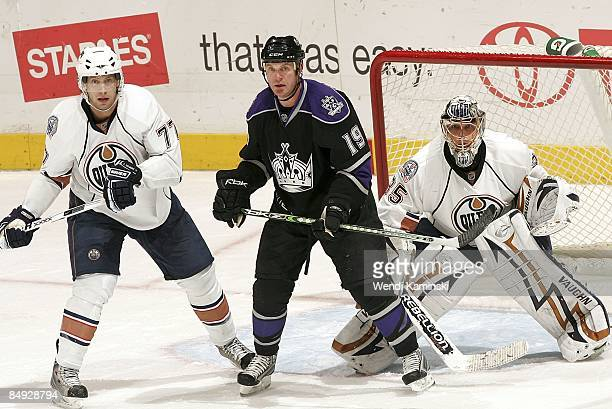 Tom Gilbert and Dwayne Roloson of the Edmonton Oilers defend in the crease against Kyle Calder of the Los Angeles Kings during the game on February...