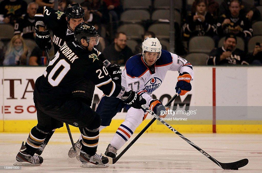 Tom Gilbert #77 of the Edmonton Oilers skates the puck past Radek Dvorak #20 of the Dallas Stars at American Airlines Center on November 21, 2011 in Dallas, Texas.