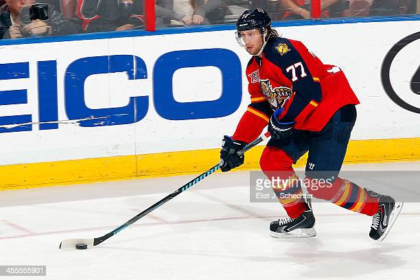 Tom Gilbert of the Florida Panthers skates with the puck against the Ottawa Senators at the BBT Center on December 3 2013 in Sunrise Florida