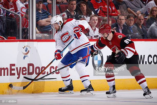 Tom Gilbert of the Montreal Canadiens attempts to control the puck under pressure from Mikkel Boedker of the Arizona Coyotes during the NHL game at...