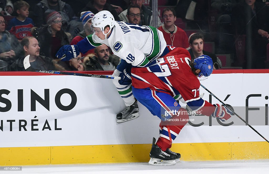Tom Gilbert #77 of the Montreal Canadiens body checks Jake Virtanen #18 of the Vancouver Canucks in the NHL game at the Bell Centre on November 16, 2015 in Montreal, Quebec, Canada.