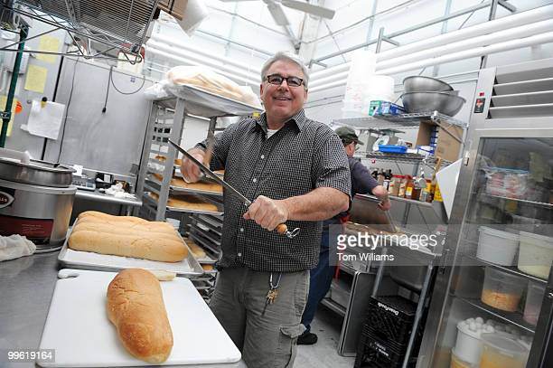 Tom Glasgow owner of Market Lunch in Eastern Market sharpens a knife to cut bread for lunch service
