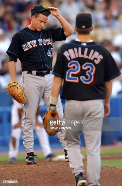 Tom Glavine of the Mets wipes his brow as teammate Jason Phillips come to the mound.