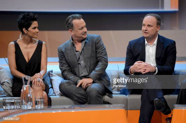 Tom Hanks and Halle Berry react to Oliver Welke during the 'Wetten dass..?' show on November 3, 2012 in Bremen, Germany.
