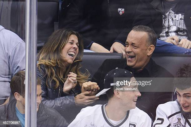 Tom Hanks and Rita Wilson laugh together at a hockey game between the Calgary Flames and the Los Angeles Kings at Staples Center on November 30 2013...