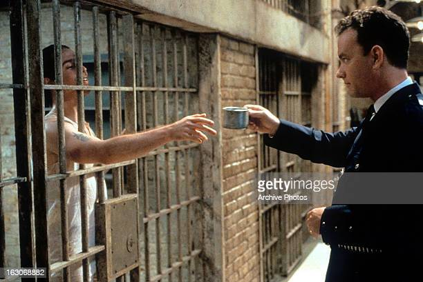 Tom Hanks hands a cup to an inmate in a scene from the film 'The Green Mile' 1999