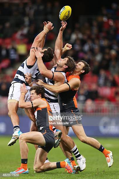 Tom Hawkins and Jimmy Bartel of the Cats compete for the ball against Phil Davis and Lachlan Plowman of the Giants during the round 18 AFL match...