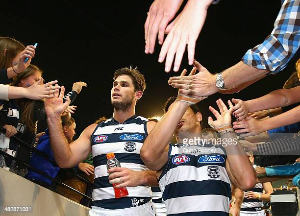 Tom Hawkins and Mathew Stokes of the Cats high five fans after winning the round three AFL match between the Collingwood Magpies and the Carlton...