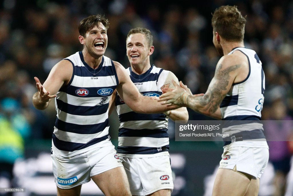 Tom Hawkins of the Cats (left) and Joel Selwood of the Cats celebrate winning with Zach Tuohy of the Cats (right) during the round 18 AFL match between the Geelong Cats and the Melbourne Demons at GMHBA Stadium on July 21, 2018 in Geelong, Australia.