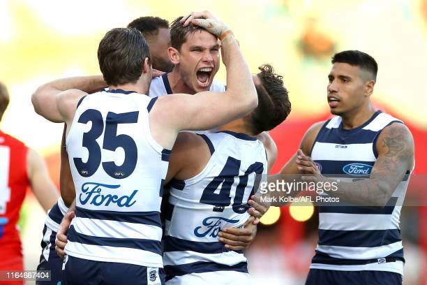 Tom Hawkins of the Cats celebrates with his team mates after kicking a goal during the round 19 AFL match between the Sydney Swans and the Geelong...