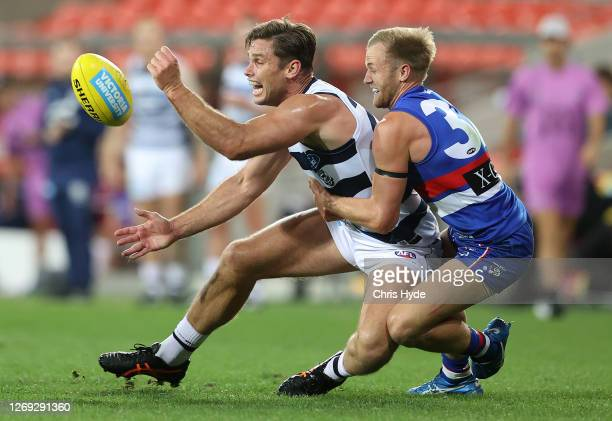 Tom Hawkins of the Cats handballs whilst being tackled by Will Hayes of the Bulldogs during the round 14 AFL match between the Western Bulldogs and...