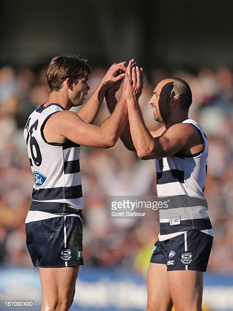 Tom Hawkins of the Cats is embraced by James Podsiadly after kicking a goal during the round 23 AFL match between the Geelong Cats and the Sydney...